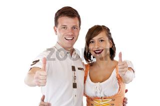 Erfolgreicher Mann und Frau im Dirndl hält Daumen nach oben. Freigestellt auf weissem Hintergrund