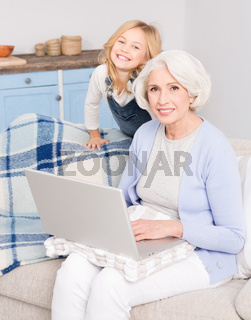 Granny and little girl using laptop