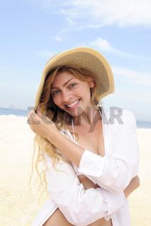 Sommer am Strand: elegante Frau mit Strohhut und Bikini