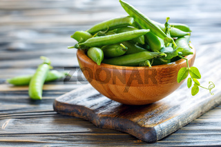 Green peas in wooden bowl.