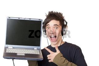 Jugendlicher mit Kopfhörer und Laptop zeigt beigeistert auf Comp