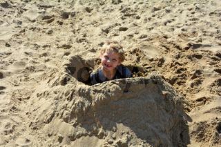 Junge hat sich in Sand eingegraben