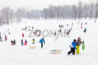 Winter fun, snow, family sledding at winter time.