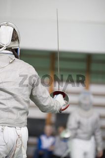 Two teenager fencers fighting with rapiers on the fencing tournament