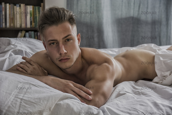 Sexy naked young man on bed