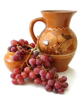 jug and red grapes over white background