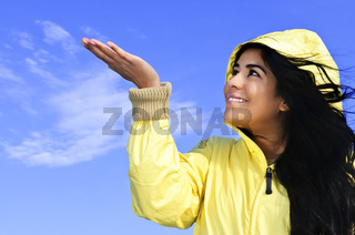 Beautiful young woman in raincoat checking for rain