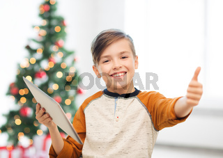 boy with tablet pc showing thumbs up at christmas