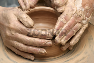 Women hands in clay at process of making  crockery on pottery wheel