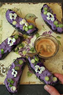 schwarze Crostini mit lila Vitelotte Kartoffel-Frischkäsecreme, Lauchzwiebeln und Hornveilchen