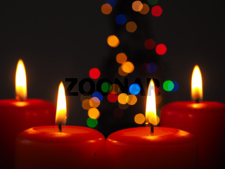 Burning Advent candles with Christmas tree lights