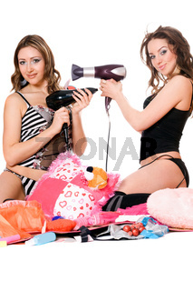 Two playful young girlfriends with hair dryers. Isolated