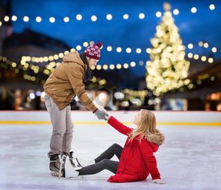 man helping woman on christmas skating rink