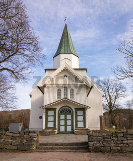 White church and blue sky with small clouds in Norway, vertical image