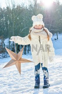 Kind hält einen Weihnachtsstern
