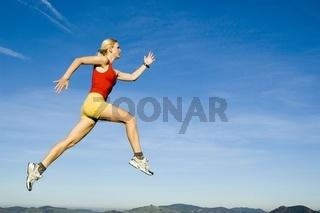 Blonde junge Frau springt beim Laufen in die Luft