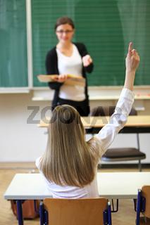 Grundschülerin  in der Grundschule zeigt auf -