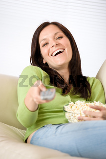 Woman pointing with television remote control