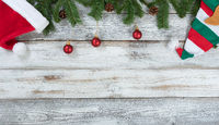 Top border of Christmas decorations on rustic white wooden background