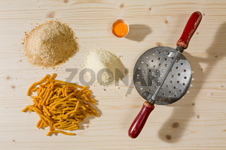 Passatelli original Italian pasta and ingredients over a wooden background