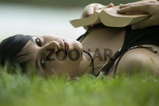 Junge Frau beim Lesen eines Buches im Freien
