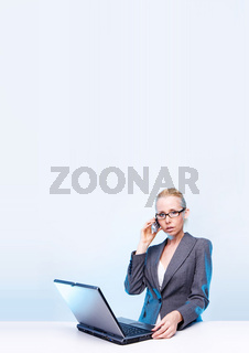 blonde businesswoman using laptop computer and mobile phone  at work