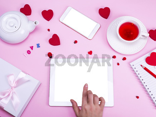 hand touches the screen of an electronic tablet with a white screen