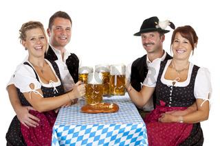 Bayrische Männer und Frauen stossen mit Oktoberfest Maß Bier an. Freigestellt auf weissem Hintergrund