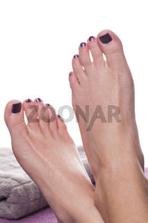 Bare feet with pedicure propped by towel