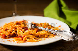 Closeup of half-eaten tagliatelle pasta with bolognese ragu