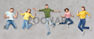 happy people or friends jumping in air over gray