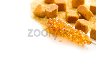 Brown amber sugar crystal on wooden stick.
