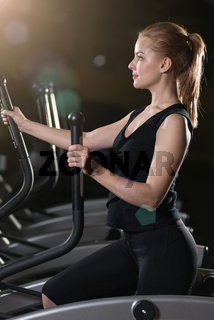Young woman at the gym exercising. Run on machine.