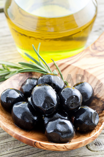 Black pickled olives on a olive wood spoon as closeup on old wood