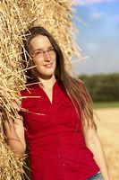 Junge Frau Stroh angelehnt mit Brille