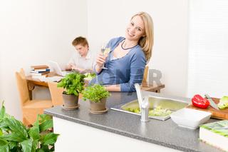 Happy woman cook enjoy white wine in kitchen