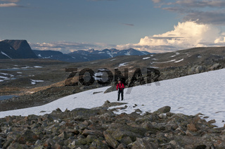 Wanderer ueberquert ein Schneefeld, im Hintergrund Gipfel im Sarek Nationalpark, Welterbe Laponia, Lappland, Schweden