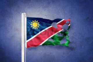 Torn flag of Namibia flying against grunge background