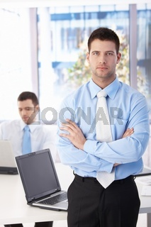 Confident businessman standing in bright office