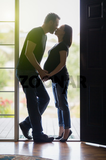 Mixed Race Pregnant Couple Kissing in Doorway.