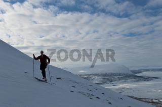 Skitourengeher beim Aufstieg im Akkamassiv, Stora Sjoefallet Nationalpark, Welterbe Laponia, im Hintergrund der zugefrorene See Akkajaure, Lappland, Schweden