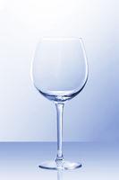 An empty red wine glass in slightly blue light