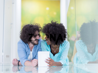 Couple relaxing together at home with tablet computer