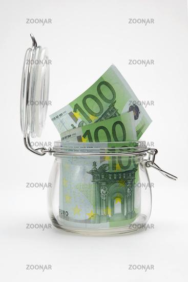 Euro bills in a glass jar