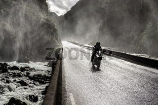 Motorbike driving fast on wet canyon valley road and bridge across river.