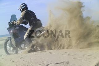 Motorradfahrer wirbelt Sand auf