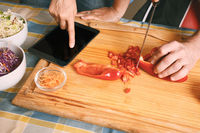 Couple cooking dinner using a digital tablet in kitchen