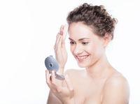 Young beautiful woman applying powder on her skin.