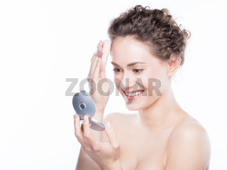 Young beautiful woman applying powder on her skin.