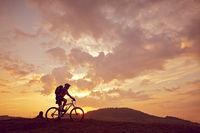Man mountain biking sunny side view